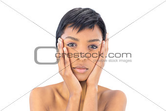 Serious black haired woman covering her cheeks with her hands