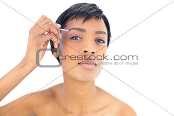 Beautiful black haired woman plucking her eyebrows