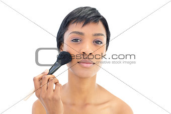 Beautiful black haired woman applying powder on her cheeks