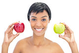 Happy black haired woman holding apples