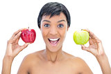 Cheerful black haired woman holding apples