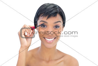 Amused black haired woman applying mascara