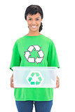 Smiling black haired ecologist holding a recycling box