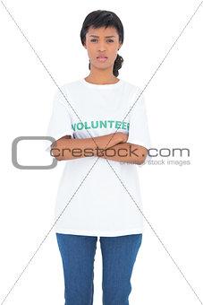 Depressed black haired volunteer posing with crossed arms