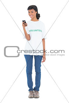 Attractive black haired volunteer texting with her mobile phone