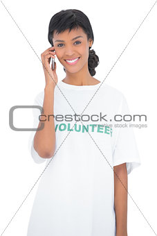 Attractive black haired volunteer calling someone with her mobile phone