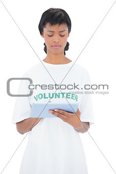 Thoughtful black haired volunteer using a tablet pc