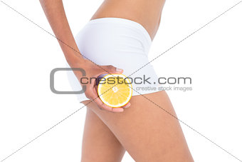 Close up of a fit woman showing half an orange