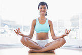 Cheerful black haired woman doing yoga
