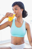 Pensive fit woman drinking a glass of orange juice