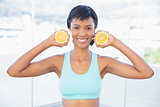 Attractive fit woman holding two halves of an orange