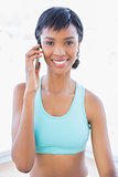 Joyful fit woman calling someone with her mobile phone
