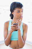 Pensive fit woman holding a mobile phone