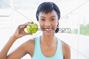Attractive black haired woman holding an apple