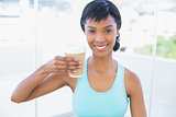 Pleased black haired woman holding a beverage