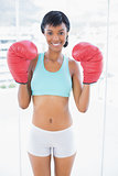 Smiling black haired woman wearing boxing gloves
