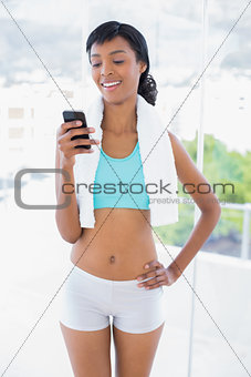Laughing black haired woman looking at her mobile phone