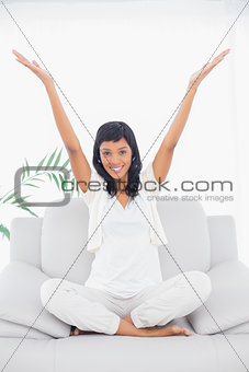 Pleased black haired woman in white clothes raising her arms