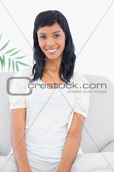 Attractive black haired woman in white clothes posing looking at camera