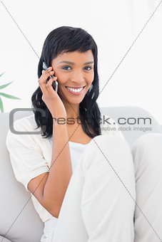 Charming black haired woman in white clothes phone calling