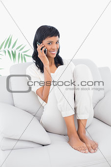 Amused black haired woman in white clothes phone calling