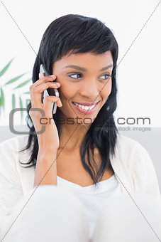 Attentive black haired woman in white clothes calling someone with her mobile phone