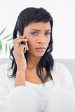 Frowning black haired woman in white clothes having a phone call