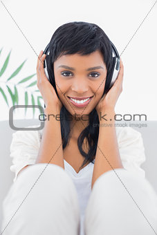 Calm black haired woman in white clothes listening to music