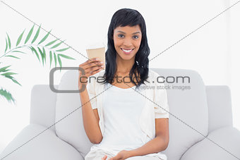 Calm black haired woman in white clothes holding a beverage