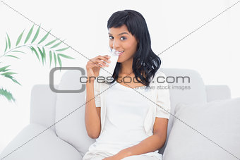 Charming black haired woman in white clothes drinking a glass of water