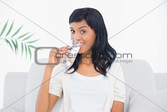 Amused black haired woman in white clothes enjoying a glass of water