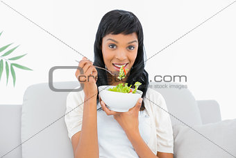 Charming black haired woman in white clothes eating salad