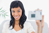Natural black haired woman in white clothes taking a picture of herself
