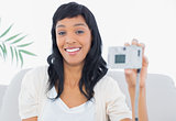 Laughing black haired woman in white clothes taking a picture of herself
