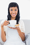 Pleased black haired woman in white clothes drinking coffee