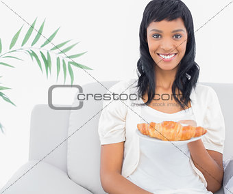 Charming black haired woman in white clothes holding a croissant