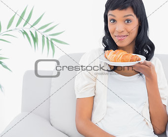 Amused black haired woman in white clothes smelling a croissant