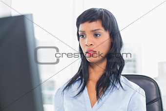 Surprised businesswoman looking at her computer