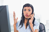 Shocked businesswoman answering the telephone