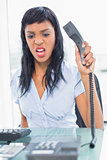 Angry businesswoman hanging up the phone