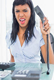 Exasperated businesswoman hanging up the phone