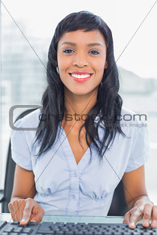 Happy businesswoman typing on a keyboard