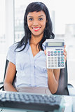 Delighted businesswoman holding a calculator