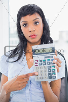 Stern businesswoman holding a calculator