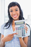 Amused businesswoman holding a calculator