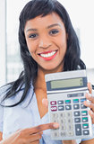 Joyful businesswoman holding a calculator