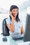 Happy businesswoman calling someone with her mobile phone