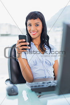 Charming businesswoman holding a mobile phone