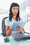 Stern businesswoman using a tablet pc