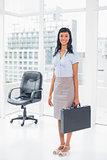 Pretty businesswoman holding a suitcase